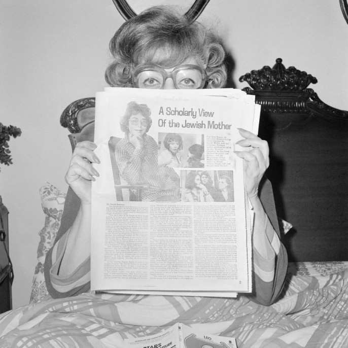 "Meryl Meisler. Mom (Sylvia """"Sunny"""" Schulman Meisler) Reading A Scholarly View of the Jewish Mother, Thanksgiving, North Massapequa, NY, November 1978. Vintage gelatin silver print, printed 1978 14 x 11 in. Signed, titled and dated by photographer verso."