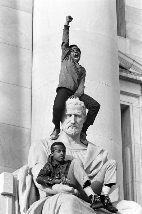 May 1, 1970 - New Haven, Connecticut, USA: Boy gives raised fist salute as he and a friend sit on a statue in front of the New Haven County Courthouse during a demonstration of 15,000 people during the Bobby Seale / Ericka Huggins trial. Bobby Seale, Chairman of the Black Panther Party is on trial along with Ericka Huggins for murder. Both are acquitted.(Stephen Shames/Polaris)