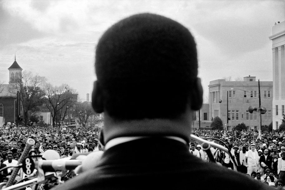 MONTGOMERY- MARCH 25: Dr. Martin Luther King, Jr. seen close from rear, speaking in front of 25,000 civil rights marchers, at conclusion of the Selma to Montgomery march in front of Alabama state capital building on March 25, 1965. In Montgomery, Alabama. (Photo by Stephen Somerstein/Getty Images)