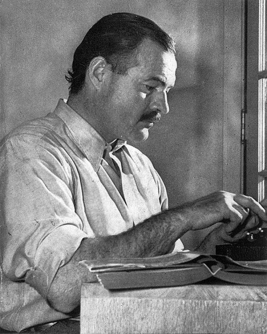 "Hemingway posing for a dust jacket photo by Lloyd Arnold for the first edition of ""For Whom the Bell Tolls"", at the Sun Valley Lodge, Idaho, late 1939. Photo by Lloyd Arnold. Courtesy of Wikimedia Commons."