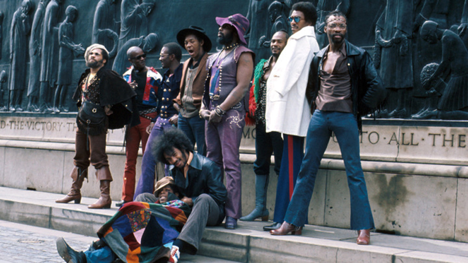 "LIVERPOOL, ENGLAND - MAY 1971: (L-R) Fuzzy Haskins, Tawl Ross, Bernie Worrell, Tiki Fulwood, Grady Thomas, George Clinton, Ray Davis, Calvin Simon and seated Eddie Hazel and Billy ""Bass"" Nelson of the funk band Parliament-Funkadelic pose for a portrait in May 1971 in Liverpool, England. (Photo by Michael Ochs Archives/Getty Images)"