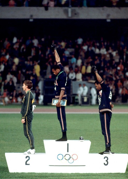 Neil Leifer (United States, b. 1942). 1968 Summer Olympics: (L-R) Australia Peter Norman (silver), USA Tommie Smith (gold), and USA John Carlos (bronze) on medal stand during Men's 200M medal presentation at Estadio Olimpico. Smith and Carlos wearing black gloves and raising fist for racial equality in USA. Black Power salute., October 16, 1968.