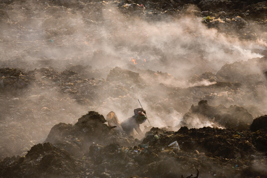 Nigel Dickinson. Fires burning below, 2007. Using fire to separate metal from plastic and rubber, a recycling worker takes advantage of the permanently smouldering rubbish inside Smokey Mountain. From the series Smokey Mountain and Recycling Phnom Penh, 2007-2010. Courtesy of artist