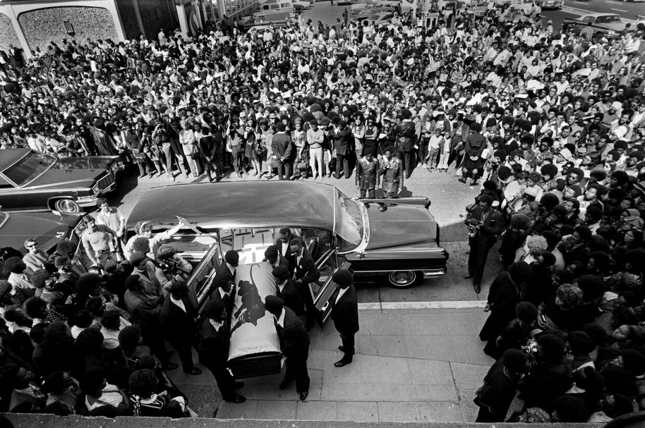 August 28, 1971 - Oakland, California, USA: Black Panthers carry George Jackson's coffin into St. Augustine's Church for his funeral service as a huge crowd watches. (Stephen Shames/Polaris)