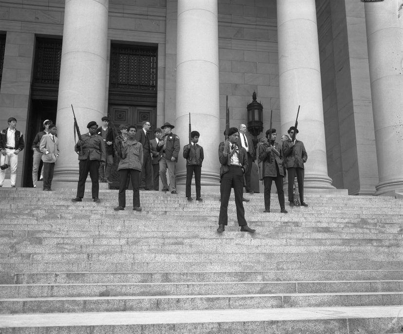 """UNKNOWN PHOTOGRAPHER, OLYMPIA, WA, FEBRUARY 1969. Washington State Archives. Armed members of the Seattle chapter of the Black Panther Party standing on the state capitol steps protesting a proposed law limiting the ability to carry firearms in a """"manner manifesting an intent to intimidate others."""""""